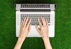 Het werk als thema heeft in openlucht: de menselijke hand toont gebaren en een open notitieboekje op een achtergrond van groene g Stock Foto's