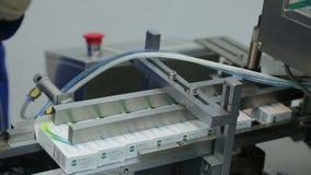 Het werk in de farmaceutische verpakkende machine van de fabrieksblaar stock footage