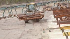 Het werk in een fabriek, het werkproces in een houtbewerkingsfabriek, het werk aangaande een bulldozer, gele bulldozer in een fab stock videobeelden