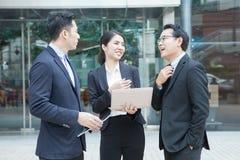 Het werk in een team Twee mannen en een vrouw bespreken het projectnieuws bij Stock Foto's