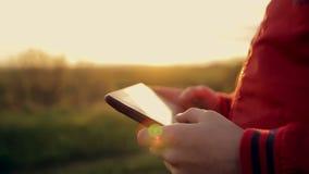Het werk en spel op de tablet bij zonsondergang in het park stock video