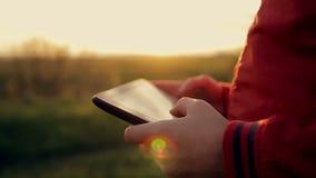 Het werk en spel op de tablet bij zonsondergang in het park stock videobeelden