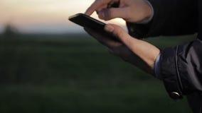 Het werk en spel op de tablet bij zonsondergang in het park stock footage
