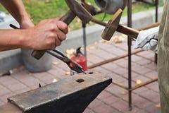 Het werk met hamers op het aambeeld stock foto