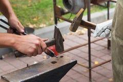 Het werk met hamers op het aambeeld stock afbeeldingen