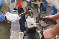 Het werk met hamers op het aambeeld royalty-vrije stock afbeelding