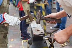 Het werk met hamers op het aambeeld in de straat royalty-vrije stock foto