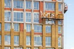 Het werk op grote hoogte aangaande de externe muren van high-rise de bouw Glaswolisolatie De arbeider isoleert het huis die zich  royalty-vrije stock afbeelding