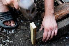 Het werk proces Mensen` s handen op het werk Het belemmeren van de raad Hulpmiddelen - een grote hamer - een voorhamer royalty-vrije stock foto