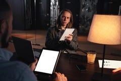 Het werk proces op het kantoor van de nachtzolder Groep jonge medewerkers die gesprek over nieuw opstarten maken Het Gesprek van  royalty-vrije stock foto's