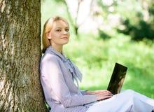Het werk profiteert in openlucht De vrouw met laptop het werk leunt in openlucht boom De notulen voor ontspannen Het meisjeswerk  stock fotografie