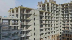 Het werk van de bouwconstructieplaats tegen blauwe hemel Arbeiders bij de bouwwerf van een flatgebouw stock videobeelden