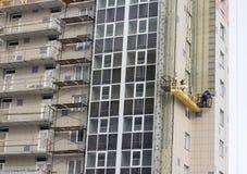 Het werk van de bouwdecoratie van de voorgevel door bouwers in een bouwwieg van nieuwe woningbouw en torenkranen royalty-vrije stock afbeeldingen
