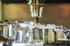 Het werk van de malenmachine in de metaalbewerkingsindustrie CNC verwerkingsdetail met smering en koelmiddel stock fotografie