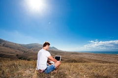 Het werk van de mens aangaande laptop in de bergen royalty-vrije stock afbeeldingen