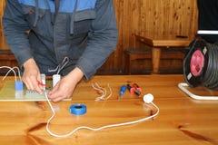 Het werk van de mensen werkend elektricien, verzamelt de elektrische kring van een grote witte straatlantaarn met draden, een rel stock foto