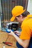 Het werk van de reparatie aangaande koelkasttoestel stock afbeelding