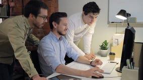 Het werk van de teamgroep aangaande de bouw van de computerarchitectuur project in bureau stock videobeelden