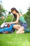 Het werk van de tuin, vrouwen maaiend gras met grasmaaier stock afbeelding