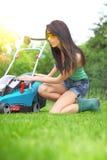 Het werk van de tuin, vrouwen maaiend gras met grasmaaier stock afbeeldingen