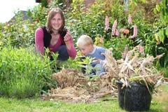 Het werk van de vrouw en van de zoon in de tuin stock afbeeldingen