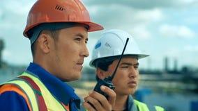 Het werk van fabrieksarbeiderscontroles in een fabriek met walkie-talkie stock video