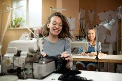 Het werk van twee vrouwennaaisters in de workshop over naaimachinesglimlach stock afbeelding