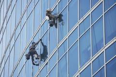 Het werk van vensterwasmachines aangaande wolkenkrabber, industriële alpinism Stock Foto