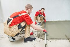 Het werk van het vloercement Oppervlakte van de stukadoor de gladmakende vloer met screeder stock afbeeldingen