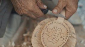 Het werk van Woodcarver in zijn workshop Het maken van houten lepel met het mes stock footage