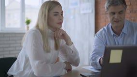 Het werk vrouw het typen op laptop en het tonen van het resultaat aan een partner 4K stock videobeelden