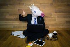 Het werk wordt gedaan! De eenhoorn in een kostuum en een band glimlacht en toont duim stock afbeeldingen