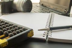 Het werkapparaten met laptops, notitieboekjes, camera's en telraam stock foto