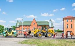 Het werkbrigade die de weg herstellen die de betonmolenhoogtepunt van het kruippakjeasfalt van verse asfaltbestrating en wegwals  royalty-vrije stock afbeelding