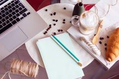 Het werkbureau met laptop, koffie en croissant Royalty-vrije Stock Afbeelding