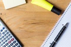 Het werkbureau met notastootkussen, calculator en biro op houten lijst stock afbeeldingen