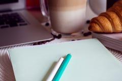 Het werkbureau met notitieboekje, laptop, koffie en croissant Royalty-vrije Stock Foto's