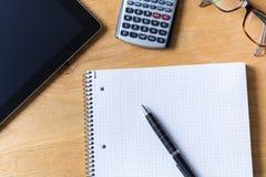 Het werkbureau met tablet, glazen, calculator en blocnote op houten royalty-vrije stock foto's