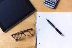 Het werkbureau met tablet, glazen, calculator en blocnote op houten royalty-vrije stock fotografie