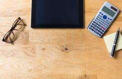 Het werkbureau met tablet, glazen, calculator en blocnote op houten royalty-vrije stock afbeeldingen