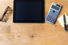 Het werkbureau met tablet, glazen, calculator en blocnote op houten stock fotografie
