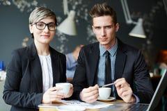 Het werken aan gezamenlijk project in koffie stock afbeelding