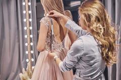 Het werken aan kleding Jonge vrouw die bruid meten terwijl binnen status royalty-vrije stock afbeelding