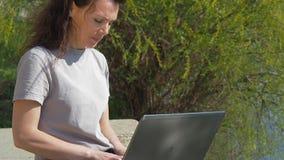 Het werken aan laptop buiten het bureau Meisje met laptop door de rivier Een gezonde zonnige dag stock video