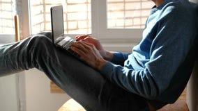 Het werken aan laptop De onherkenbare jonge mens sterting om in zijn laptop zitting aan balkon dichtbij het venster te werken stock videobeelden