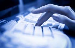 Het werken aan toetsenbord met blauwe tint royalty-vrije stock afbeeldingen