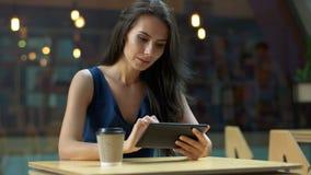 Het werken bij de koffie De jonge mooie lange zitting van de haarvrouw bij de lijst en het gebruiken van tabletcomputer in openlu Stock Fotografie