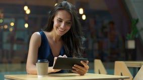 Het werken bij de koffie De jonge mooie lange zitting van de haarvrouw bij de lijst en het gebruiken van tabletcomputer in openlu Stock Afbeeldingen
