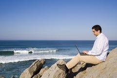 Het werken met laptop bij het strand stock fotografie