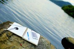 Het werken met notitieboekje bij rivieroever Royalty-vrije Stock Foto